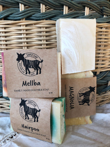 labeled goat milk soaps in front of a basket