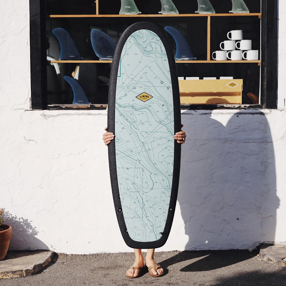 Person standing with an R series Almond blue foam board size 5'4. Has a long board center fin display coming out of a surf shop window on a white wall.
