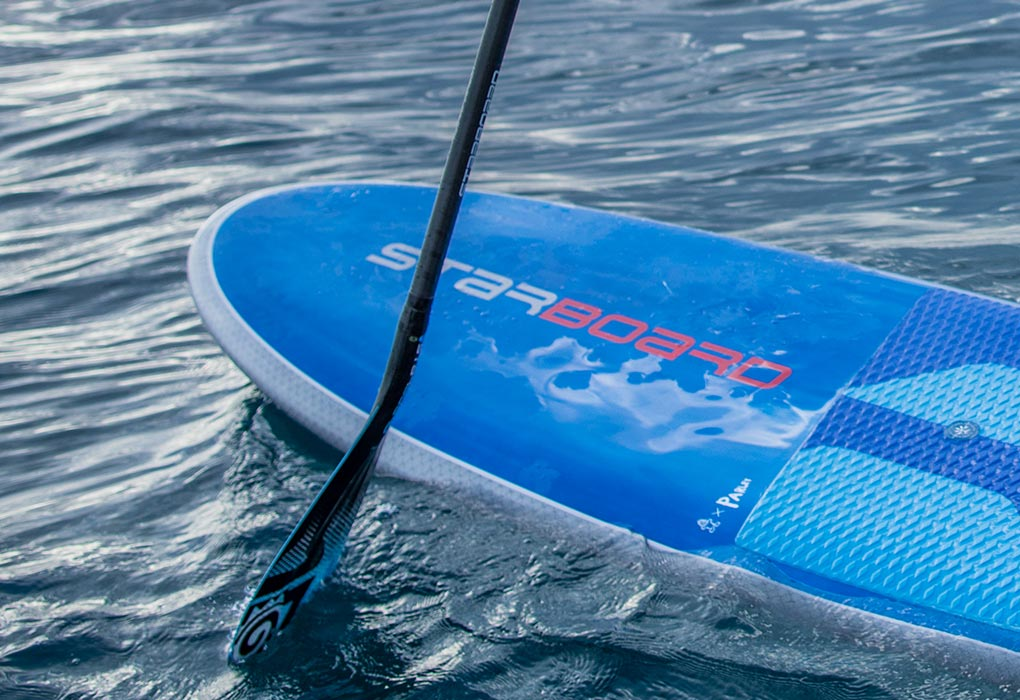 2019 Starboard Blend paddle board's nose and paddle floating on water