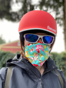 photo of person in winter bike gear, red helmet, mirrored sunglasses, Chrome rain jacket and a bini mask made out of japanese cute fabric