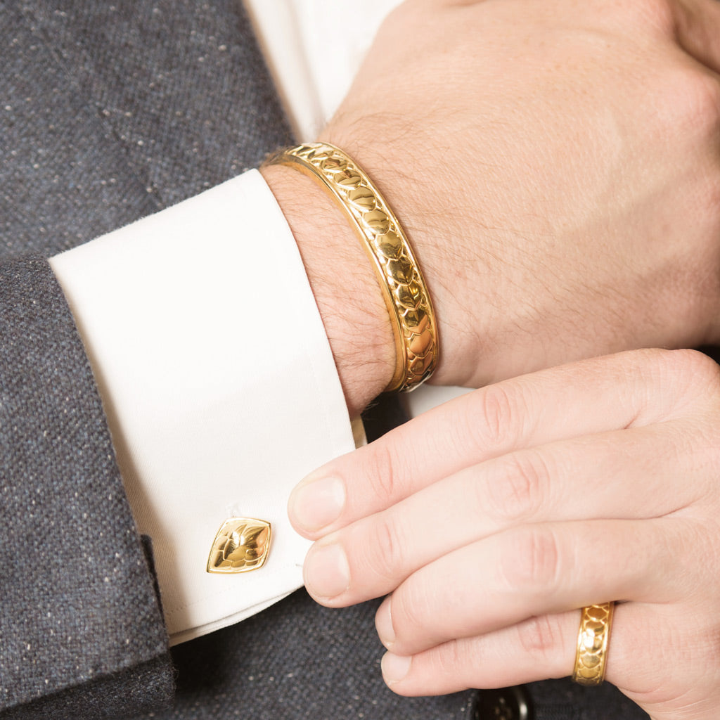Model Wearing Pangolin Shield Cufflinks in 18ct Gold, Pangolin Shield Bangle in 18ct Gold and Pangolin Shield Ring in 18ct Gold