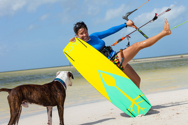 kiteboarding instructor on beach with dog