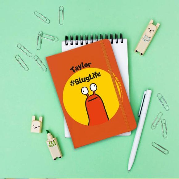Personalised Flossy and Jim #sluglife Orange Notebook. Lifestyle Image with stationery.
