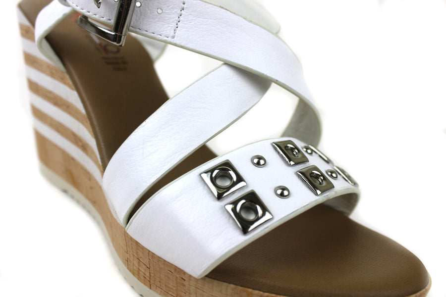 Repo 55255, Open toe wedge with an ankle Strap Closing. Colour White. One Strap across the top of the foot with Silver embellishments, a crisscross strap across the foot for extra support. Shoe Style International