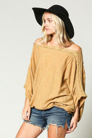 Over-sized, shapeless fit knit sweater featuring an off shoulder braided detail.