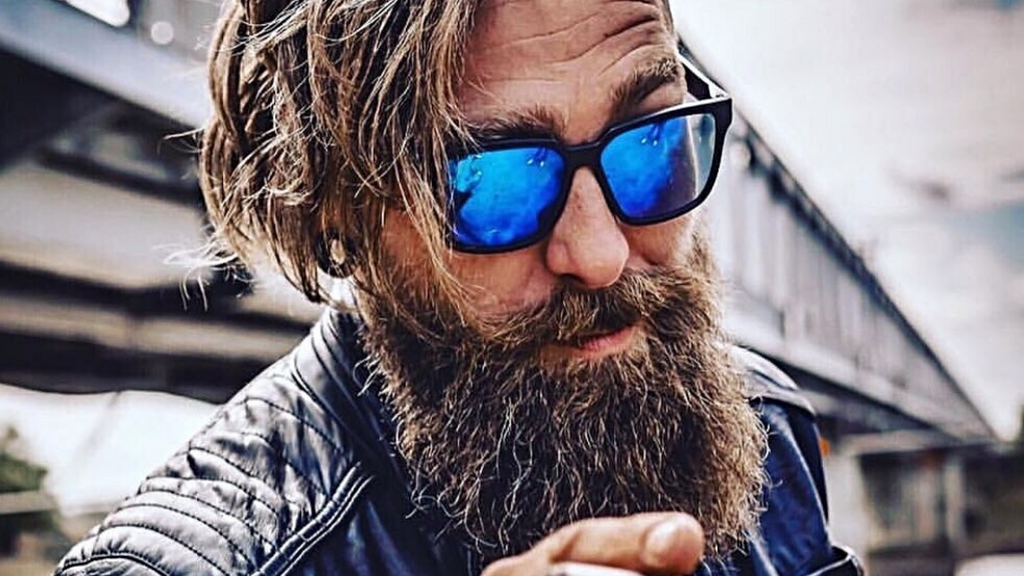 bearded man with blue sunglasses and long hair smoking a cigar