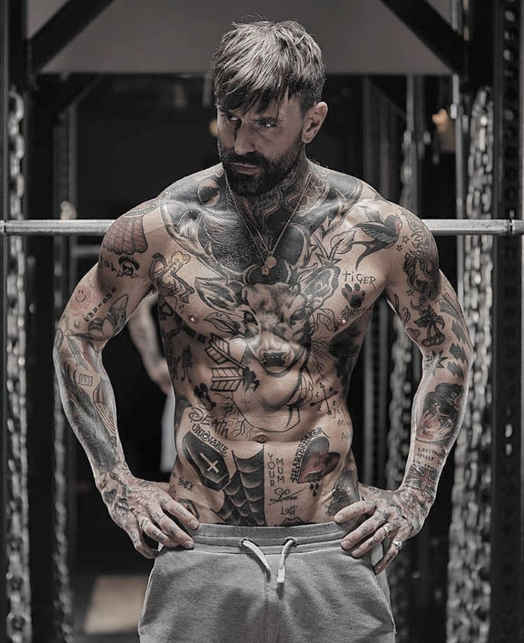 heavily tattooed bearded man at the gym surrounded by metal weights