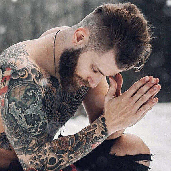 Tattooed man with beard praying in the snow