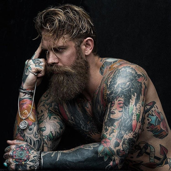 bearded man modeling with tattoos whilst staring into the distance