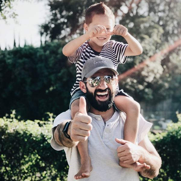 Smiling child on bearded mans back with the mans thumbs up
