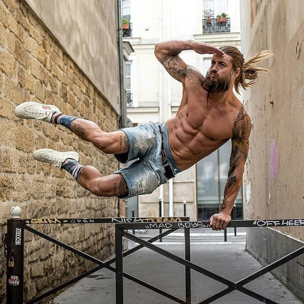 topless bearded man vaulting over a fence whilst looking into the distance