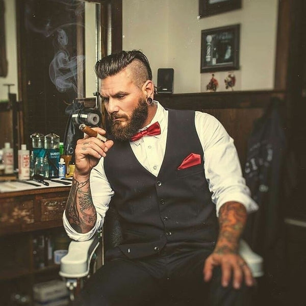 bearded man sitting on a barber chair smoking a cigar in an old fashion room