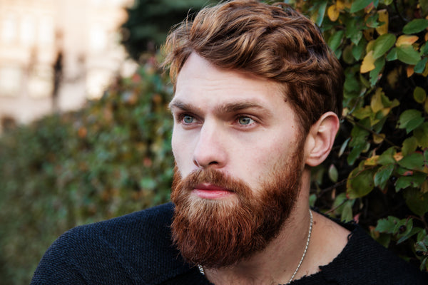 man with ginger beard looking into the distance sitting next to a green bush