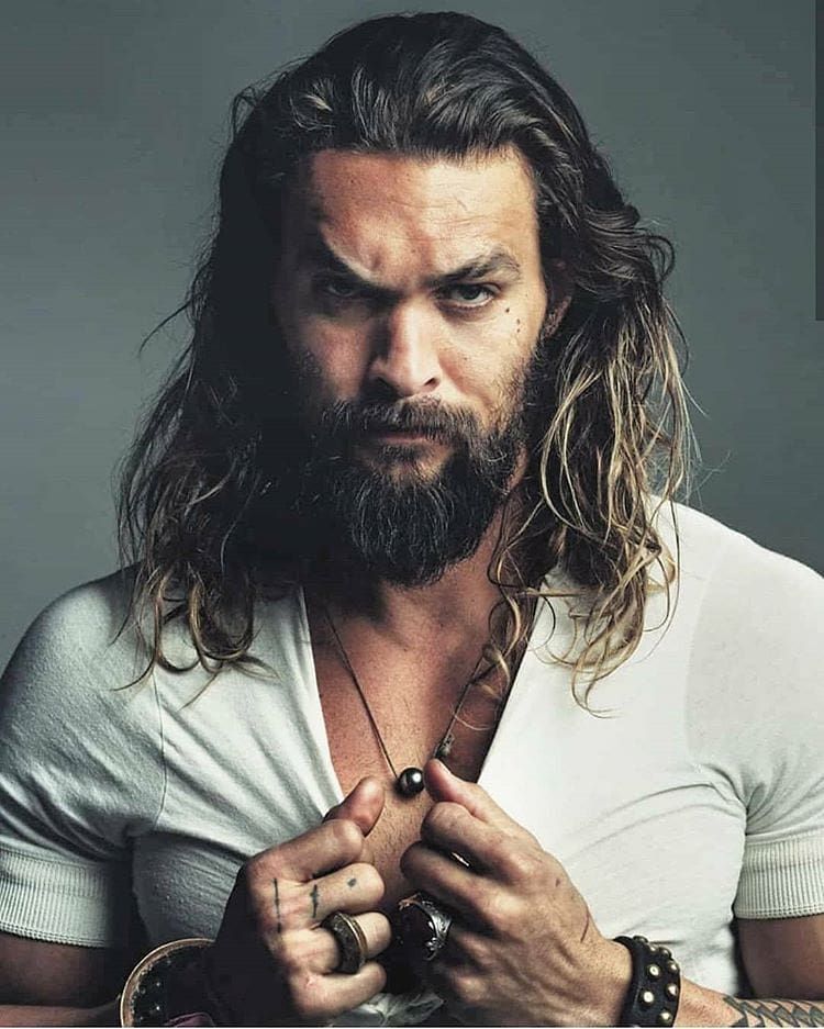 Beard model wearing a white te shirt with long hair and a necklace