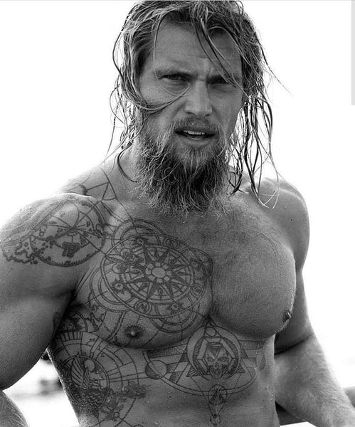 Tattooed man emerging from water with long hair