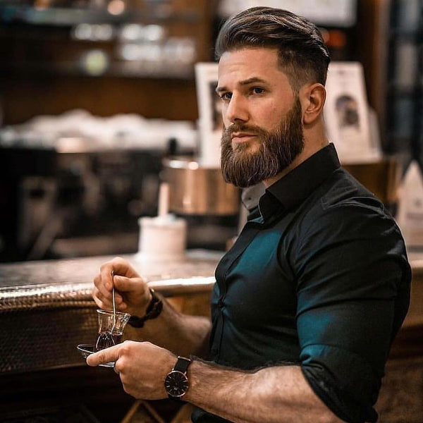 Bearded man sitting at a bar with a coffee