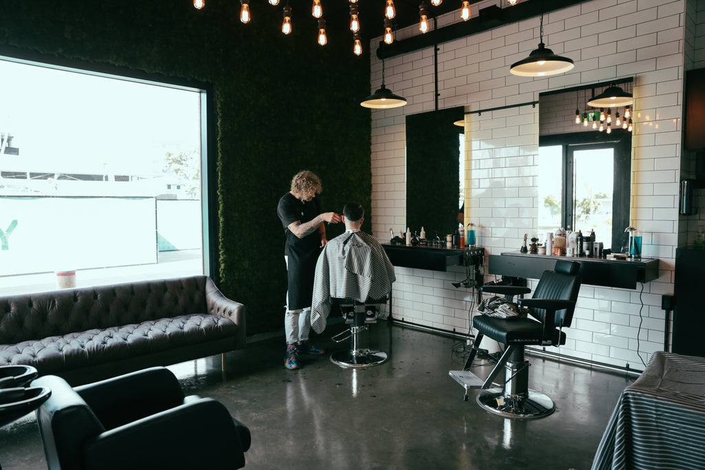 New Zealand barber cutting mans hair next to leather chair