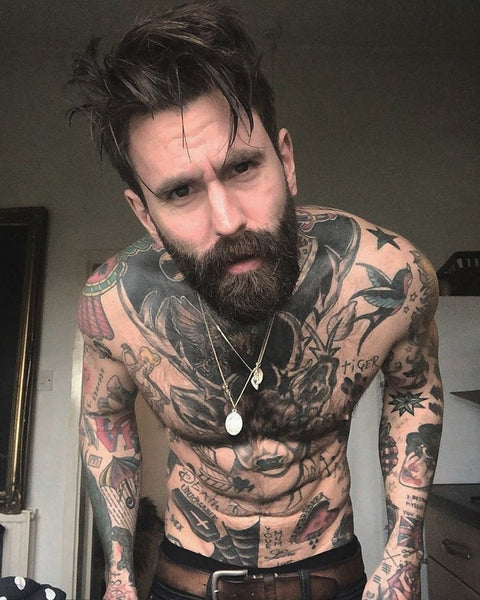 Tattooed man with bearded staring curiously at the camera