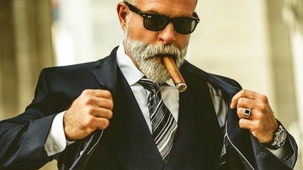 man with grey beard smoking a cuban cigar wearing a black suit with black glasses