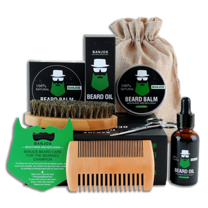 beard care kit containing one beard oil, one beard balm, one pair of beard trimmers, one brush and one beard comb in black packaging with green beard shaped banjos beards logo