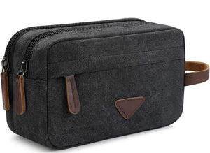 Side view of the black mens toiletry bag with brown leather accents and three seperate pockets as well as leather carrying strap