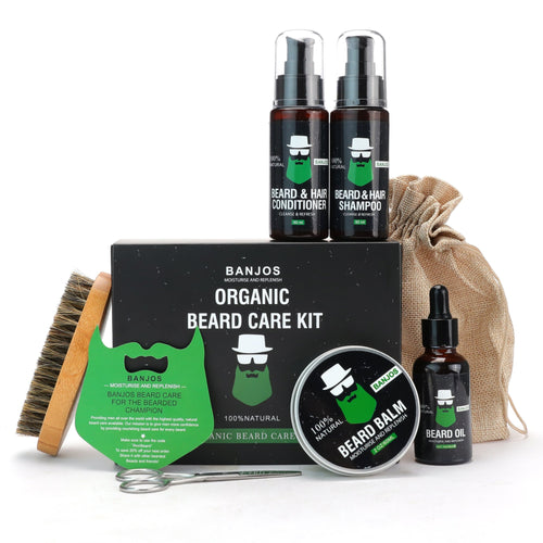 beard grooming kit beard wash and beard conditioner bottle sitting on top of black box with banjos beards logo in gree. Beard oil, beard balm, beard comb and trimmers and next to the box.