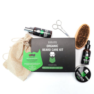 beard growth kit containing beard oil, organic beard conditioner, beard balm, beard trimmers, beard brush and a comb with black and green banjos beards branding that reads organic beard care kit