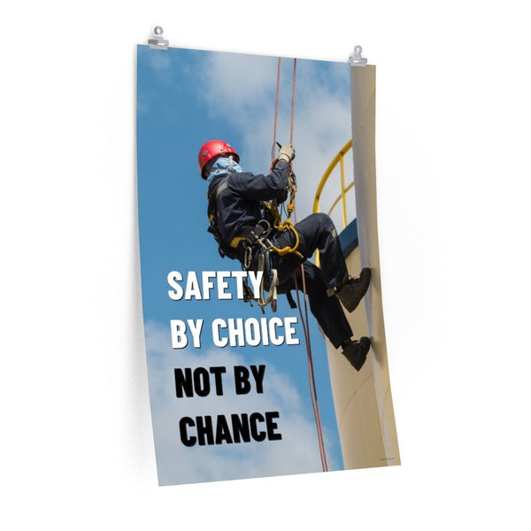 A fully harnessed man wearing a hard hat scaling the side of a building with a bright blue sky and clouds in the background with the text safety by choice, not by chance in bold text to his left.-Poster-24″ × 36″