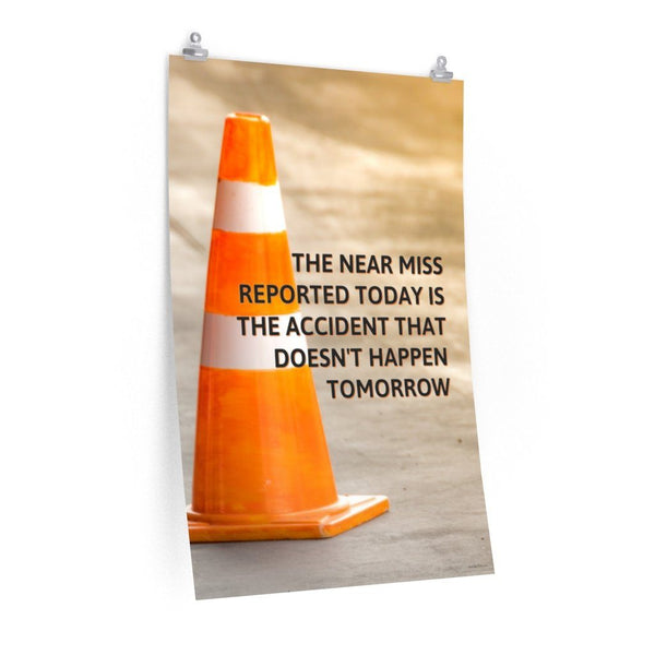 A workplace safety poster showing an orange safety cone with the slogan the near miss reported today is the accident that doesn't happen tomorrow.