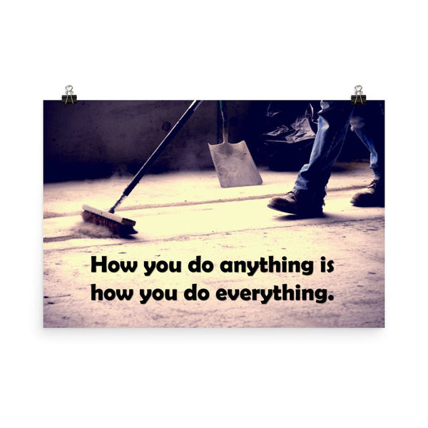Safety poster showing a closeup of the ground where a warehouse or construction worker is sweeping the workshop floor and an encouraging safety slogan written in bold text.