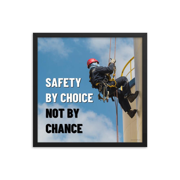 A fully harnessed man wearing a hard hat scaling the side of a building with a bright blue sky and clouds in the background with the text safety by choice, not by chance in bold text to his left.-Framed-18×18