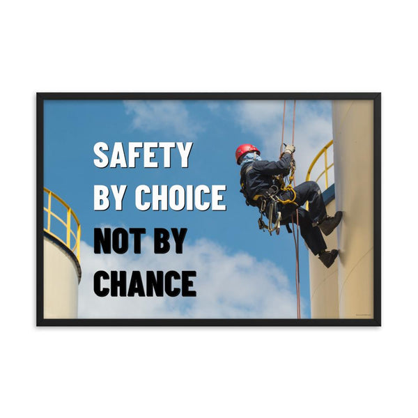 A fully harnessed man wearing a hard hat scaling the side of a building with a bright blue sky and clouds in the background with the text safety by choice, not by chance in bold text to his left.-Framed-24×36