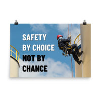 A fully harnessed man wearing a hard hat scaling the side of a building with a bright blue sky and clouds in the background with the text safety by choice, not by chance in bold text to his left.-Poster-24×36
