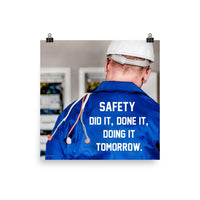 Safety poster showing an electrician wearing a hard hat and holding cables working on an electrical panel with text on the back of his bright blue shirt.
