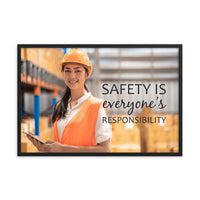 A workplace safety poster showing a young warehouse worker in a yellow hardhat and orange reflective vest holding a clipboard and smiling with the slogan safety is everyone's responsibility.