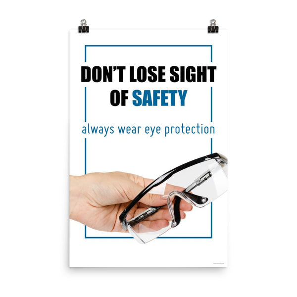 An eye safety slogan showing a close up of a hand presenting out safety glasses with a safety slogan in blue text above.