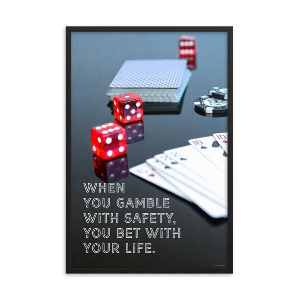 A workplace safety poster of a glossy black table with red dice, playing cards, and poker chips strewn everywhere with a safety slogan in the bottom left corner.