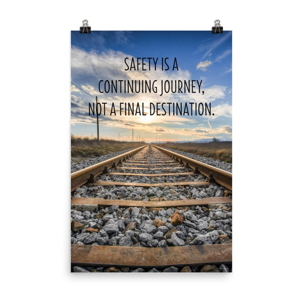 A workplace safety poster depicting old railroad tracks leading into a cloudy horizon with the text safety is a continuing journey, not a final destination.