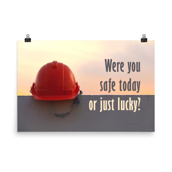 A workplace safety poster showing a red hard hat sitting on a grey wall with a dreamy sunset background and the slogan were you safe today, or just lucky?