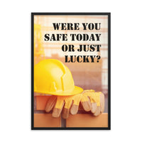 A workplace safety poster showing a yellow hard hat and some gloves sitting on a brick wall on a construction site with the slogan were you safe today, or just lucky written in black stencil font.