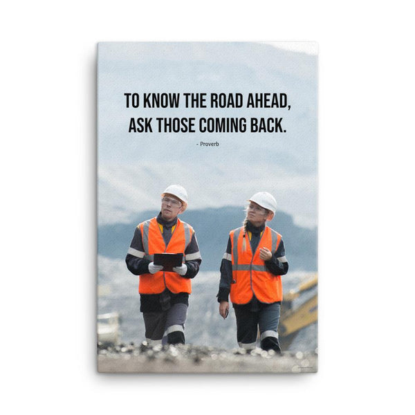 A safety poster showing two workers in reflective vests collaborating on a construction site with the proverb to know the road ahead ask those coming back.