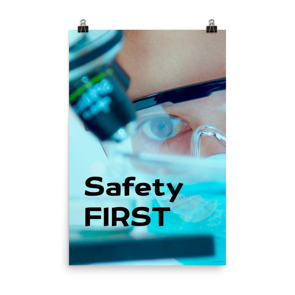 A safety poster showing a close up of a lab worker's eyes examining a sample on a microscope while wearing safety glasses and a mask with the slogan safety first in bold letters.