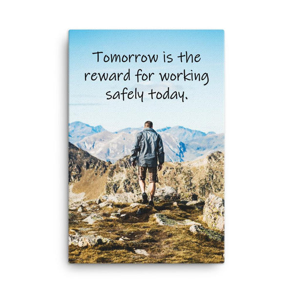 A workplace safety poster showing a man standing on a peak of a mountain with a bright blue sky and mountains behind him with the slogan tomorrow is the reward for working safely today.