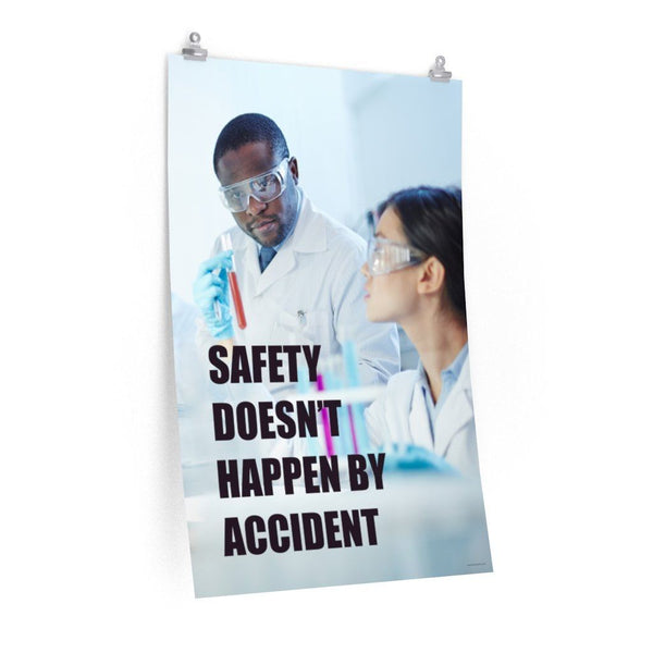 Male and female workers wearing lab coats and safety glasses while inspecting a test tube with a safety slogan written in bold text.
