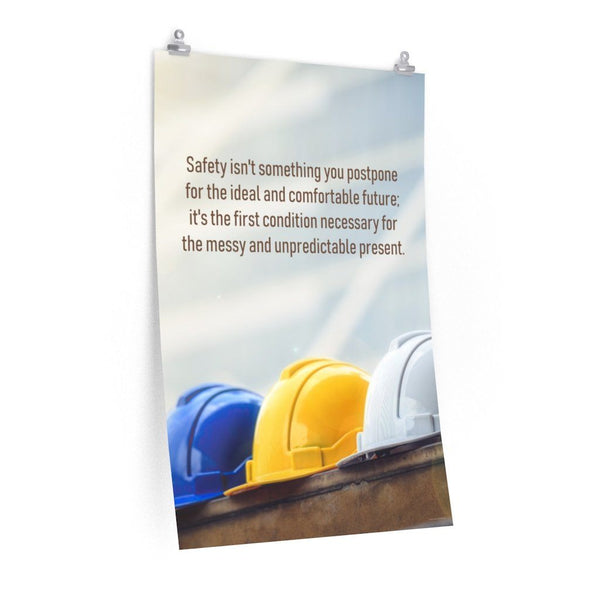 A workplace safety poster showing 3 multi colored hardhats sitting on a wall with the slogan safety isn't something you postpone for the ideal and comfortable future. It's the first condition necessary for the messy and unpredictable present.