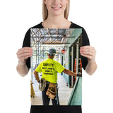 Safety poster showing a construction worker under scaffolding wearing a tool belt, hard hat, safety gloves, and bright yellow shirt with text on the back of his shirt.