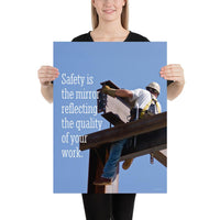 A workplace safety poster showing a construction ironworker on steel beams in a hardhat and safety harness with a bright blue sky in the background with the slogan safety is the mirror reflecting the quality of your work.
