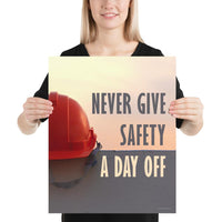 A workplace safety poster depicting a red hard hat sitting on a concrete wall with a dreamy pink sunset in the background with the text never give safety a day off to the right.