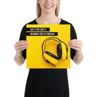 A hearing protection safety poster depicting bright yellow ear muffs on a bright yellow background in the bottom right corner with a bold safety slogan in the upper left corner.