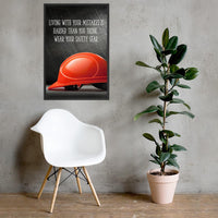 A workplace safety poster showing a bright red hard hat with an ominous black background with the slogan living with your mistakes is harder than you think, wear your safety gear.